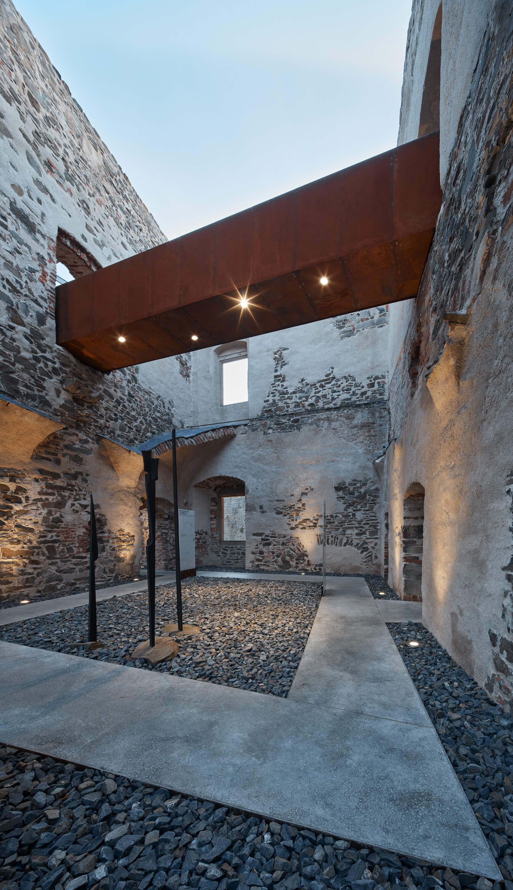 An open to sky chamber of the castle showcasing corten steel walkways on the second floor, and concrete floor boards on the ground | Helfštýn Castle Palace Reconstruction | Atelier-r | STIRworld