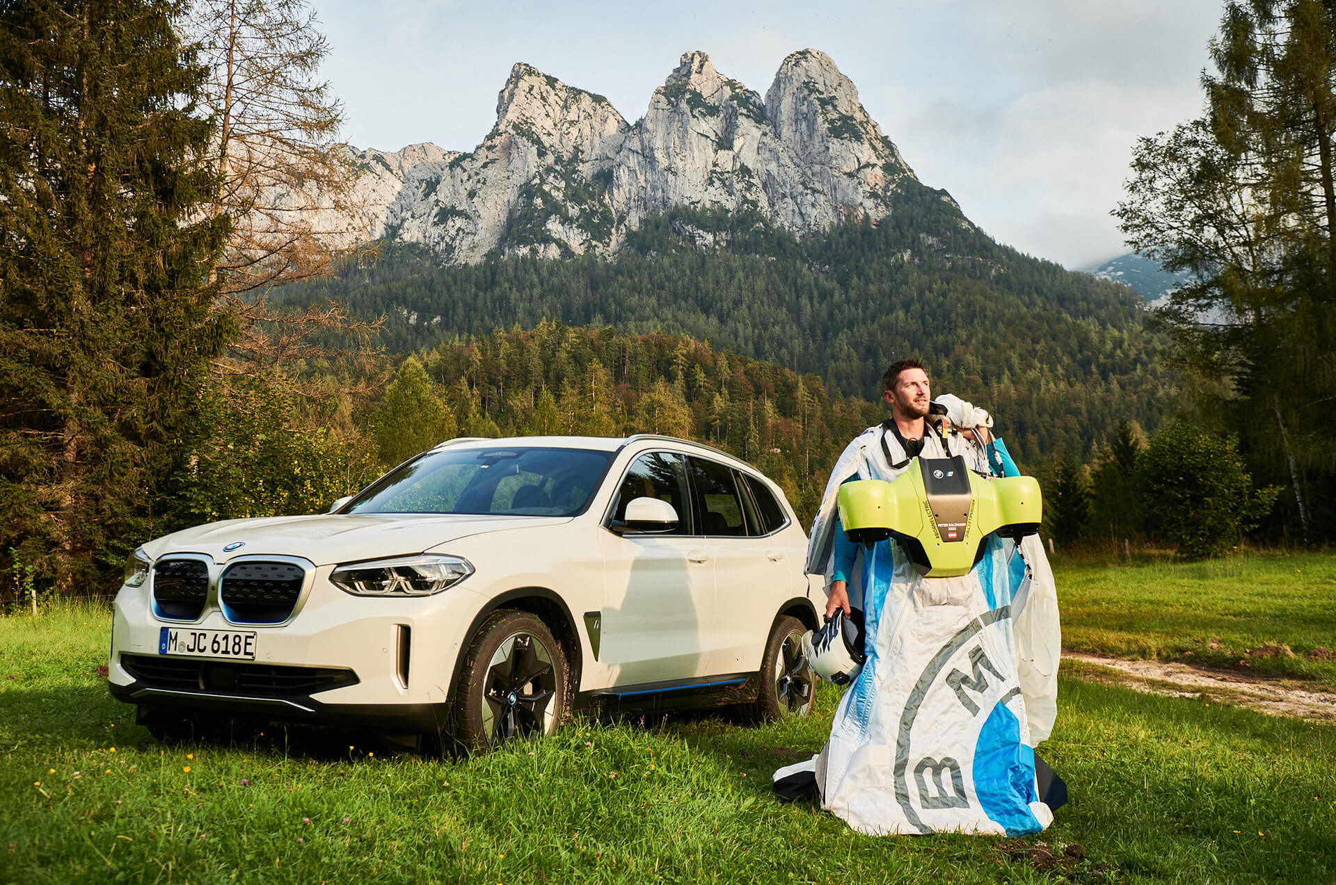 Peter Salzmann triumphantly standing in front of the iX3 post flight with the electrified wingsuit | Electrified Wingsuit | BMWi, Designworks, Peter Salzmann | STIRworld