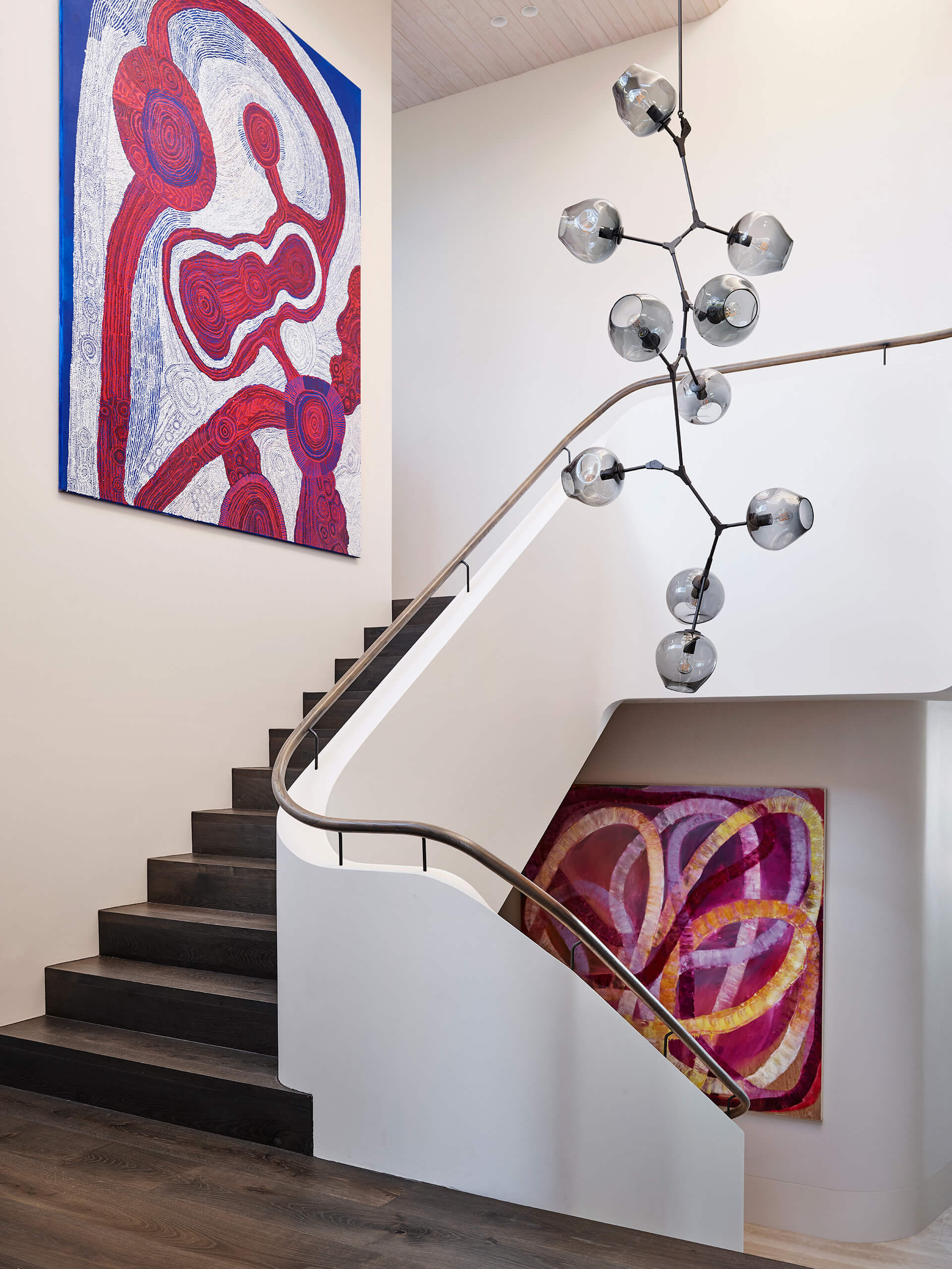 The organic stairwell is complemented by a five-meter tall branched drop pendant fixture | Hill House Interiors | Decus Interiors | STIRworld
