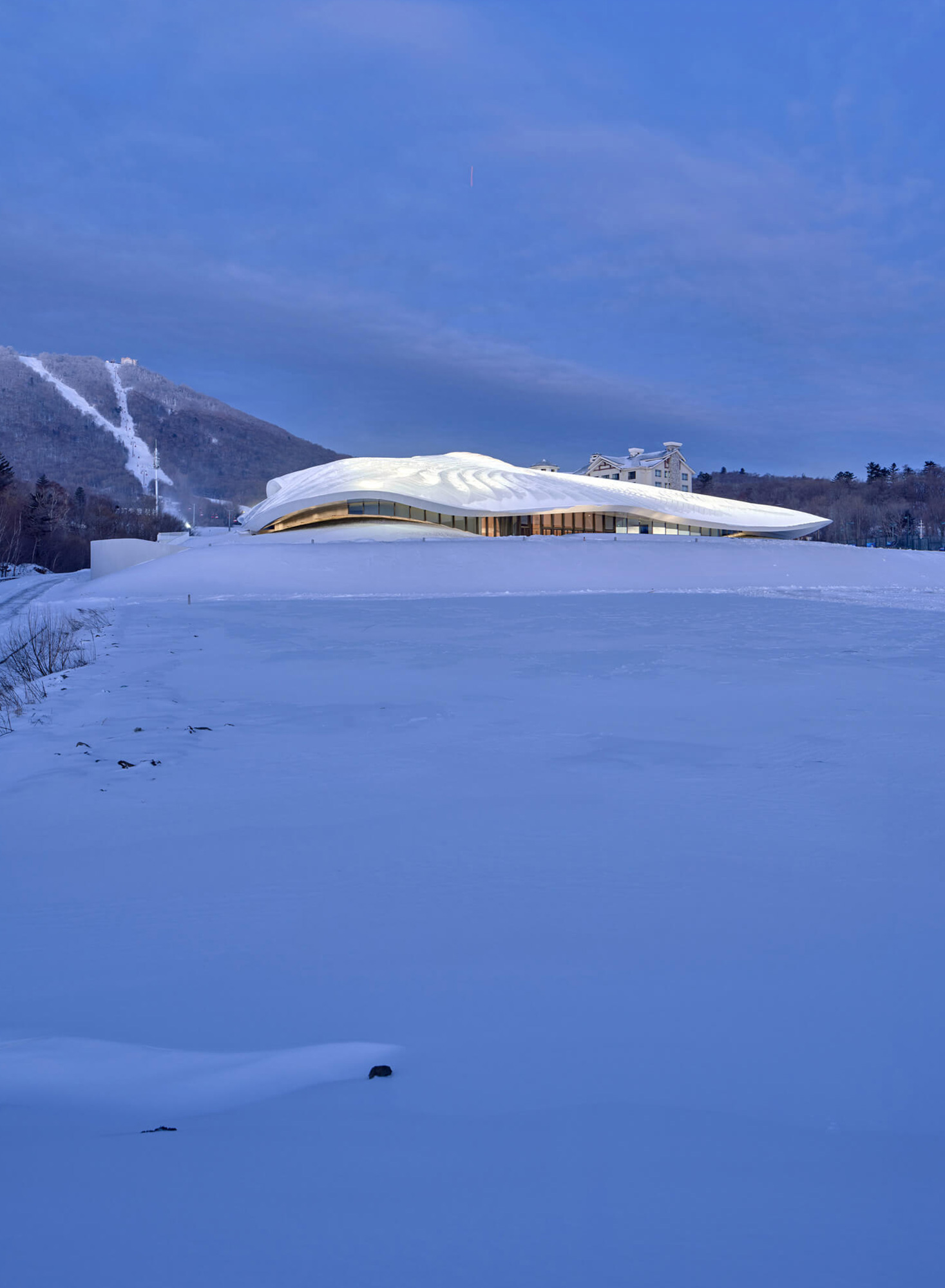 The white, flowy form mirrors and blends into the snowy landscape | Yabuli Entrepreneurs' Congress Center designed by MAD Architects | STIRworld