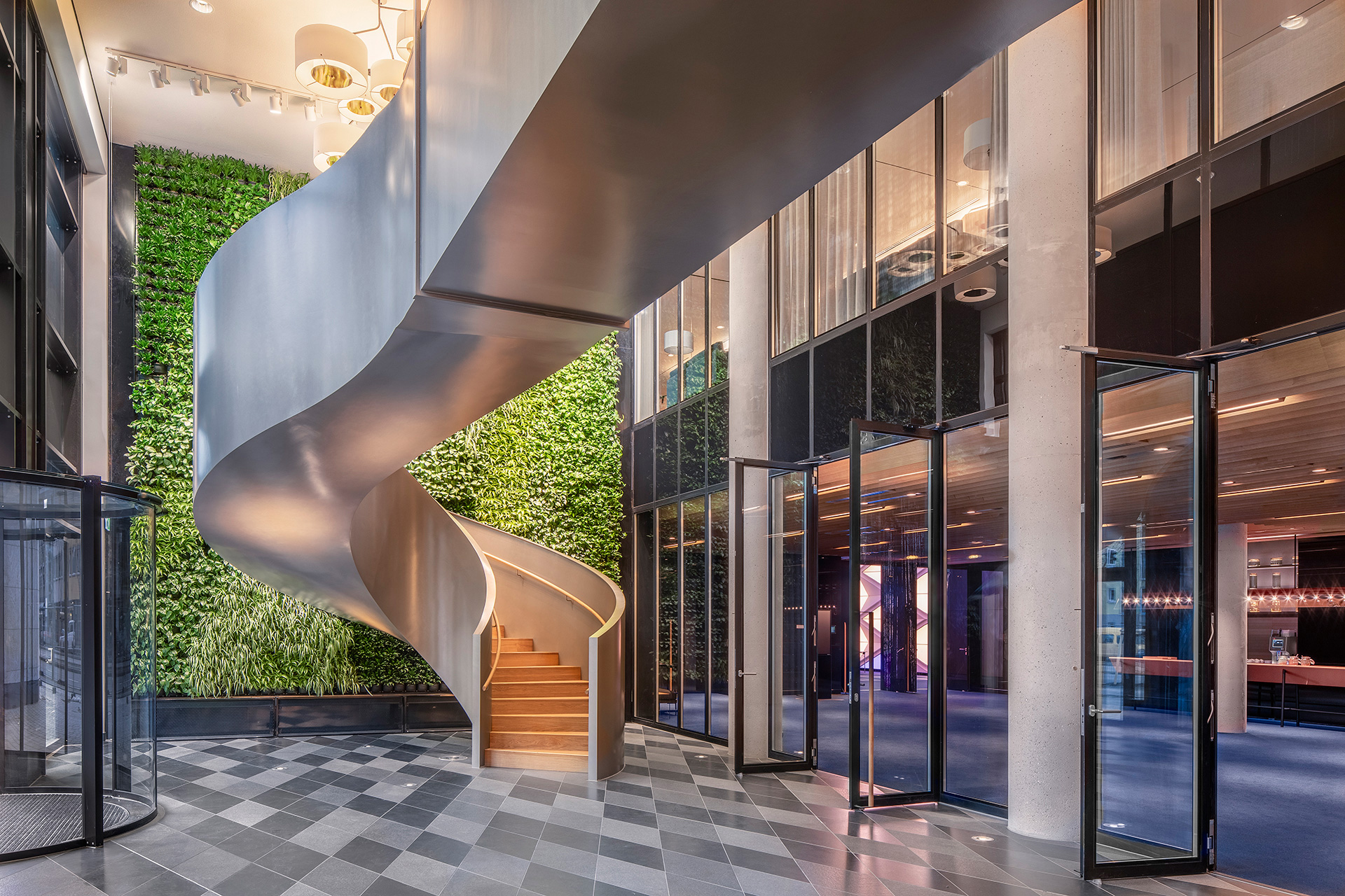 A two-storey green wall at the entrance provides a leafy frame for the iconic curved steel staircase| Andaz Munich Schwabinger Tor| Concrete| STIR
