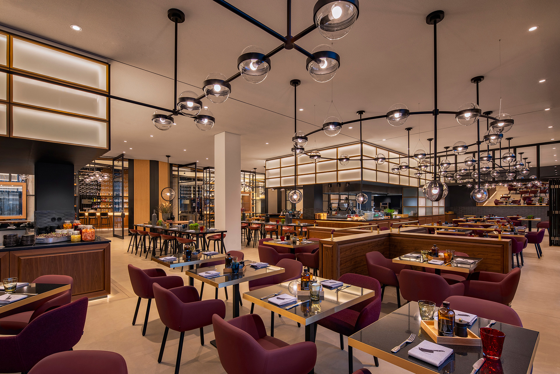 At the heart of the Lonely Broccoli restaurant is its open kitchen, which is connected to the lounge with an iconic glass display wall| Andaz Munich Schwabinger Tor| Concrete| STIR