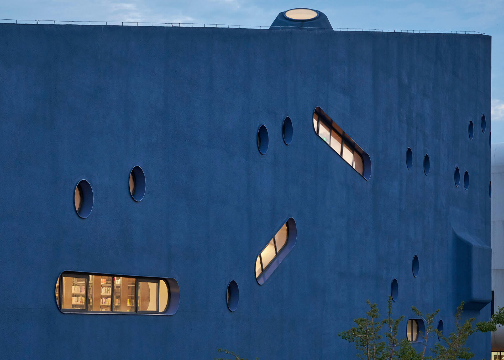 The building's façade is lined by circular and pill shaped fenestrations, akin to a ship's portholes | Pinghe Bibliotheatre| OPEN Architecture | STIRworld