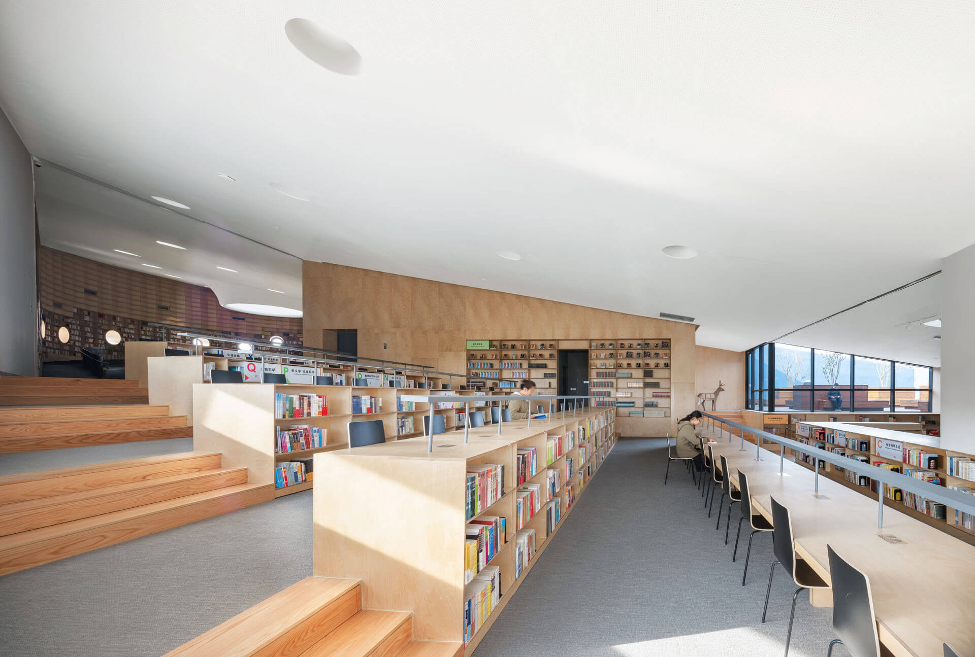 The library's terraced seating is responsive to the theatre's proscenium beneath | Pinghe Bibliotheatre| OPEN Architecture | STIRworld