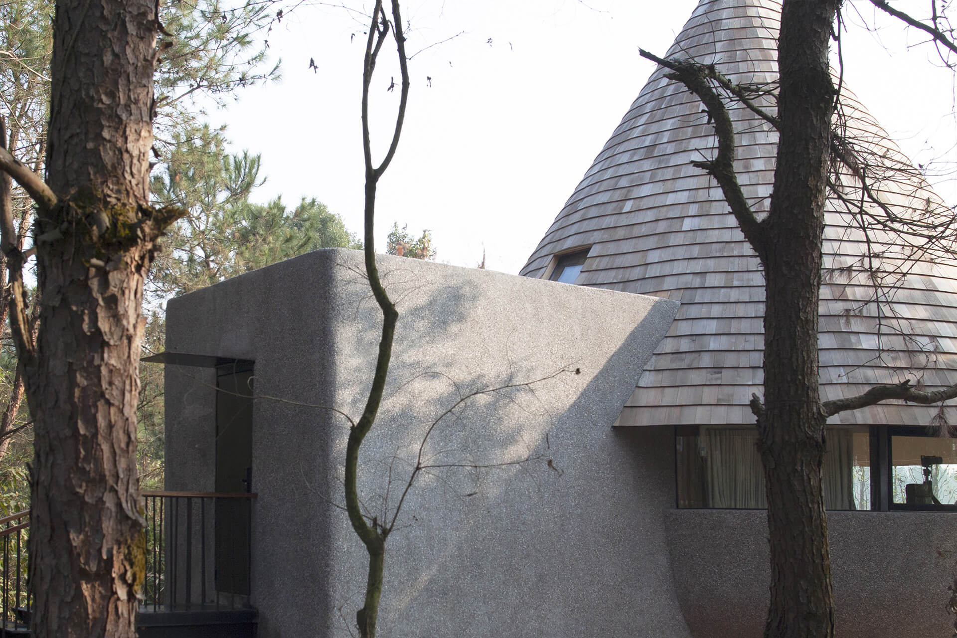 The house's form consists of two intersected volumes coated with granolithic concrete crowned by a towering conical roof clad in pinewood panels  |ZJJZ | China | STIRworld