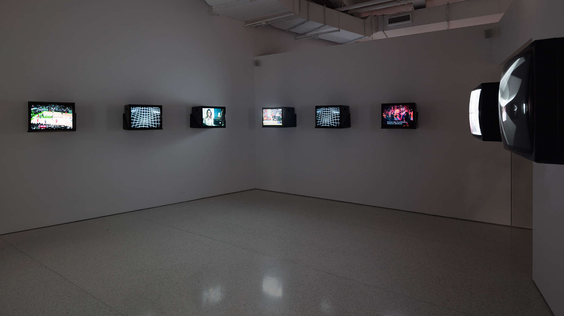 Aggressive Witness - Active Participant, 1990, live television broadcast on 8 monitors, vinyl lettering; black and white computer-generated film on 4 monitors; 19:41 min with soundtrack by Stuart Argabright. Installation view of Gretchen Bender: So Much Deathless at Red Bull Arts New York, 2019| Gretchen Bender | STIR