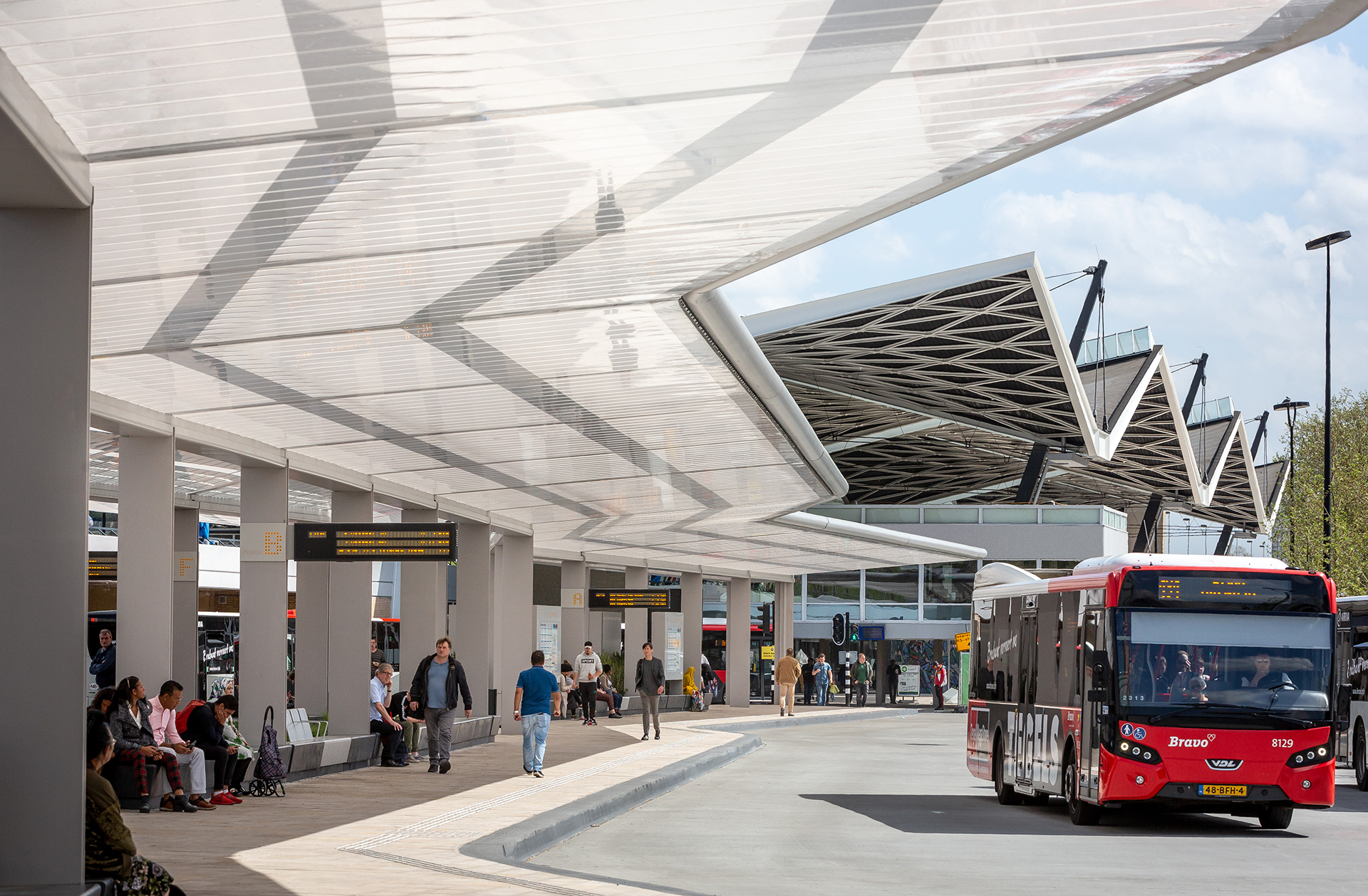 The awning of the Tilburg bus station consisting of a steel framework covered with ETFE-foil provides covers not only the bus platforms and but additionally part of the buses thereby sheltering the travellers from extremities of the weather| Tilburg Bus Station| Cepezed| STIR