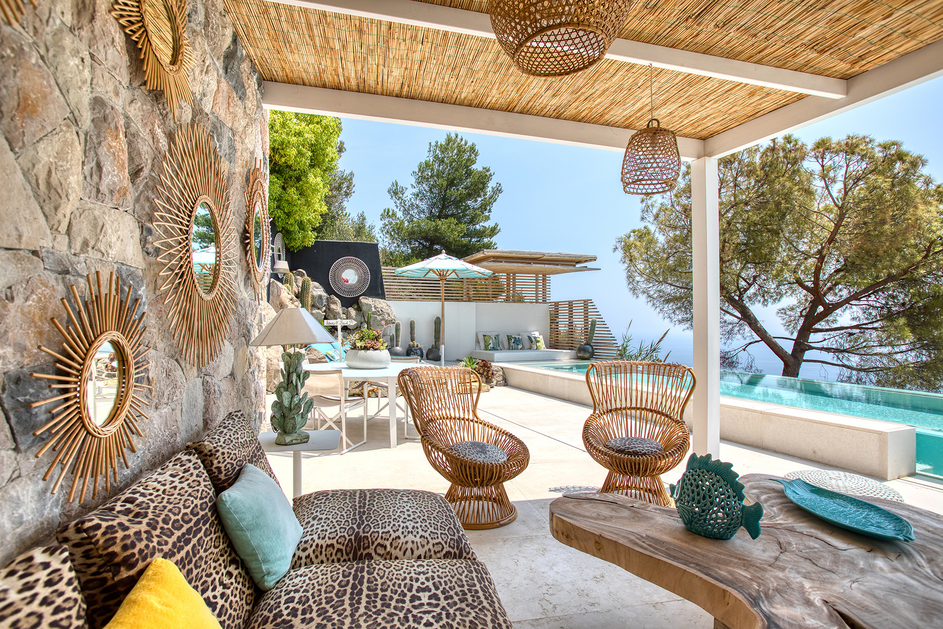 The antique rattan lights and mirrors teamed with the Paola Lenti poofs and the Roberto Cavalli animal print fabric are off-set beautifully by the cerulean water of the pool | Villa Riviera | Sabrina Monteleone-Oeino | STIR