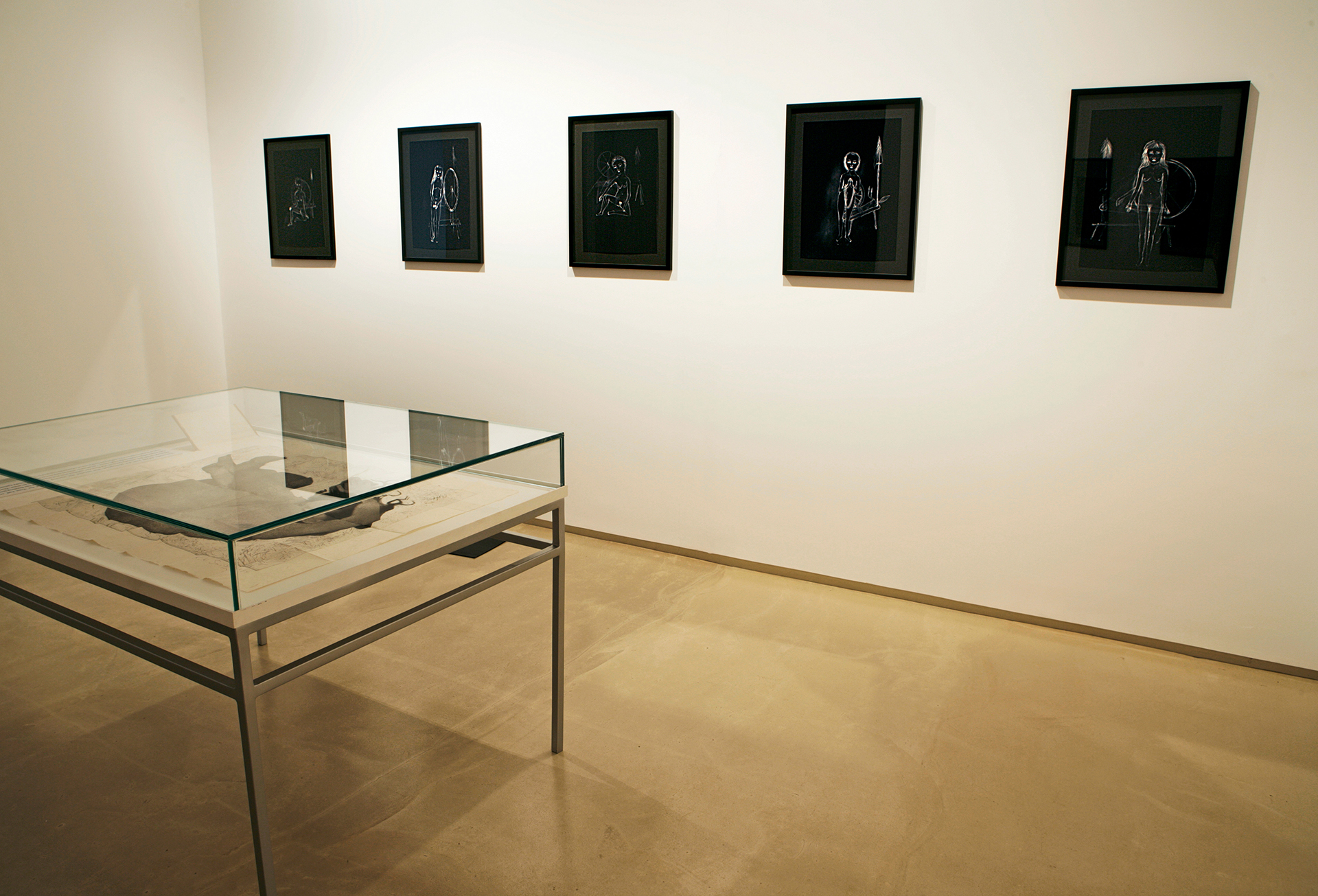 Kiki Smith, a glass case displaying image and text, works from the black work series, at Galerie Mirchandani + Steinruecke | Kiki Smith | Galerie Mirchandani + Steinruecke | STIRworld