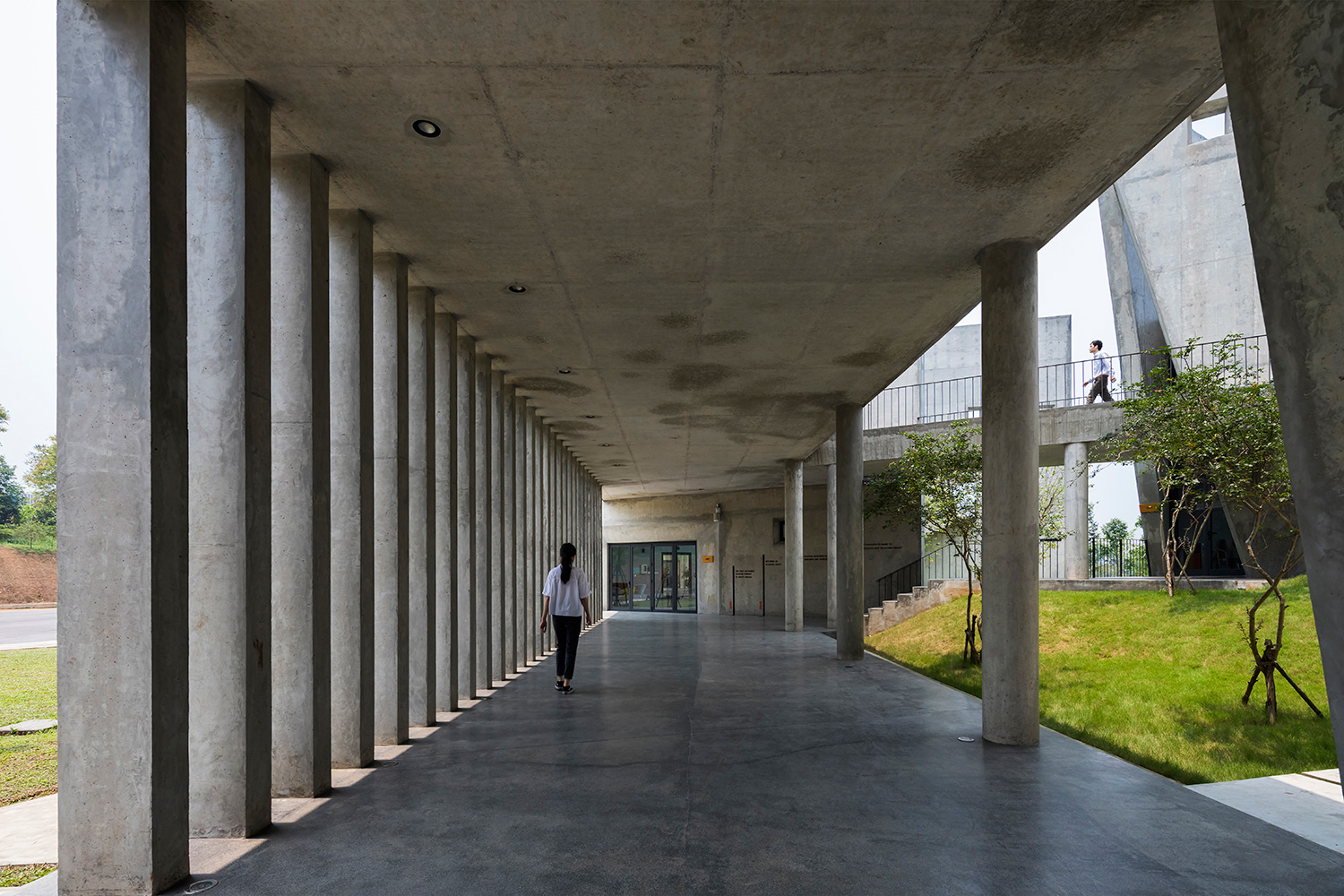 Shaded corridors flanked by concrete columns facilitate circulation between various blocks on the ground floor | Viettel Offsite Studio | VTN Architects | STIRworld
