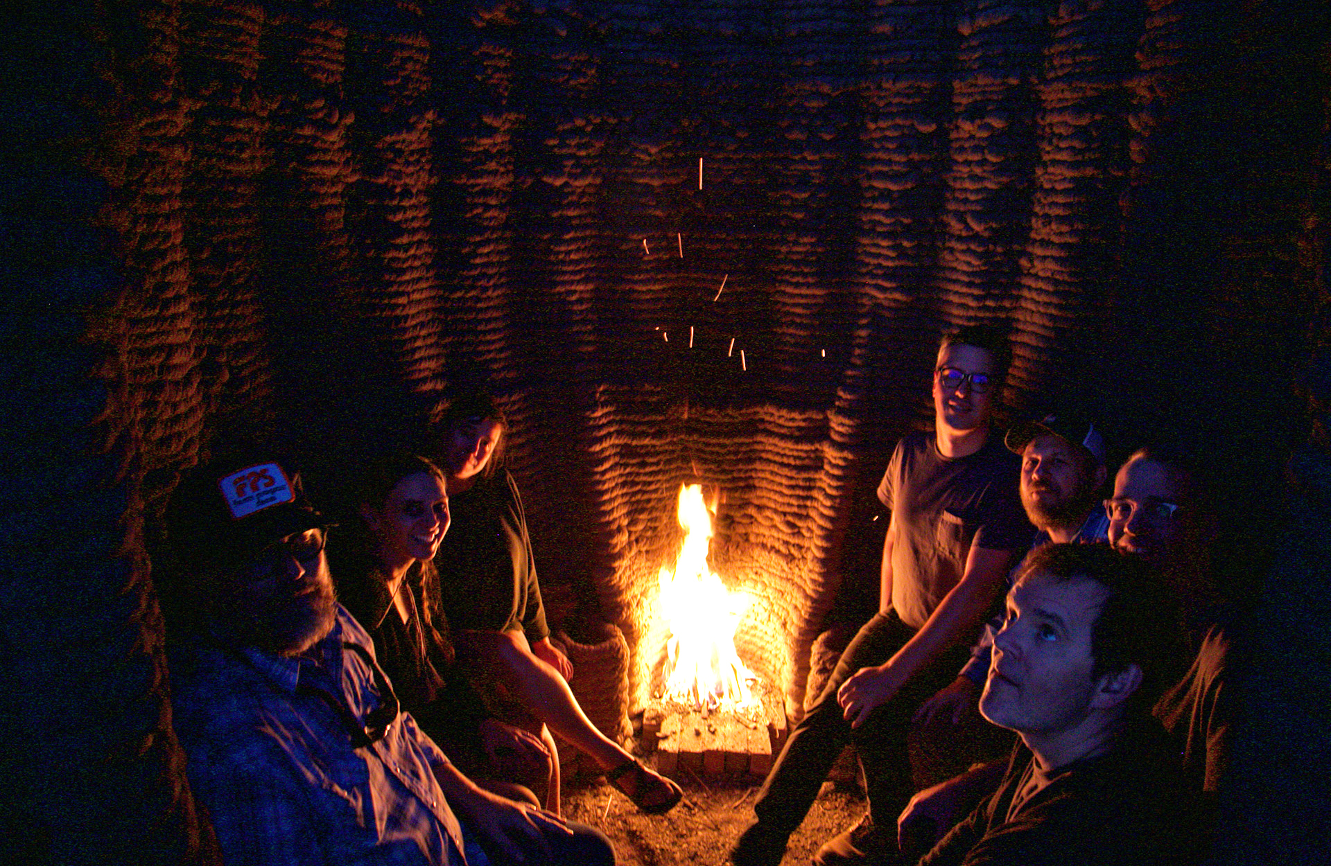 Emerging Objects' team inside the 'Hearth' that features an adobe bench and a fireplace | Mud Frontiers | Emerging Objects | STIRworld