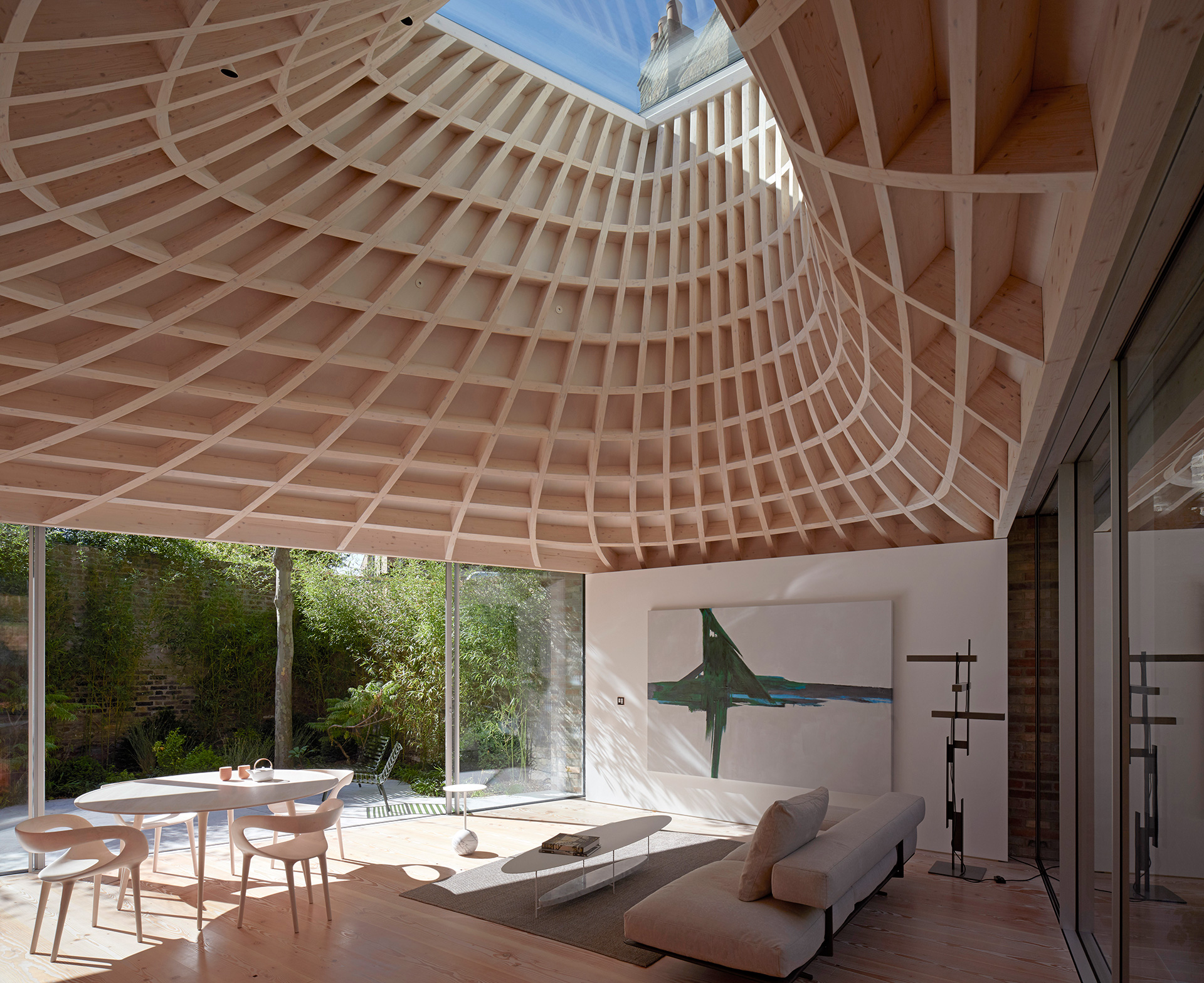 The double curvature glulam timber roof concludes in a glazed oculus | House in a Garden, London by Gianni Botsford Architects | STIRworld