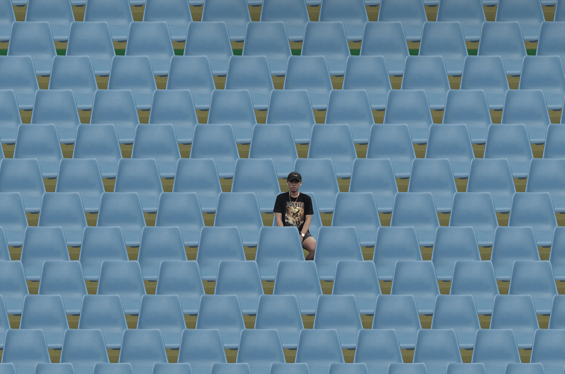 Captured here is a man sitting between a sea of empty blue chairs | Andhika Ramadhian | STIRworld