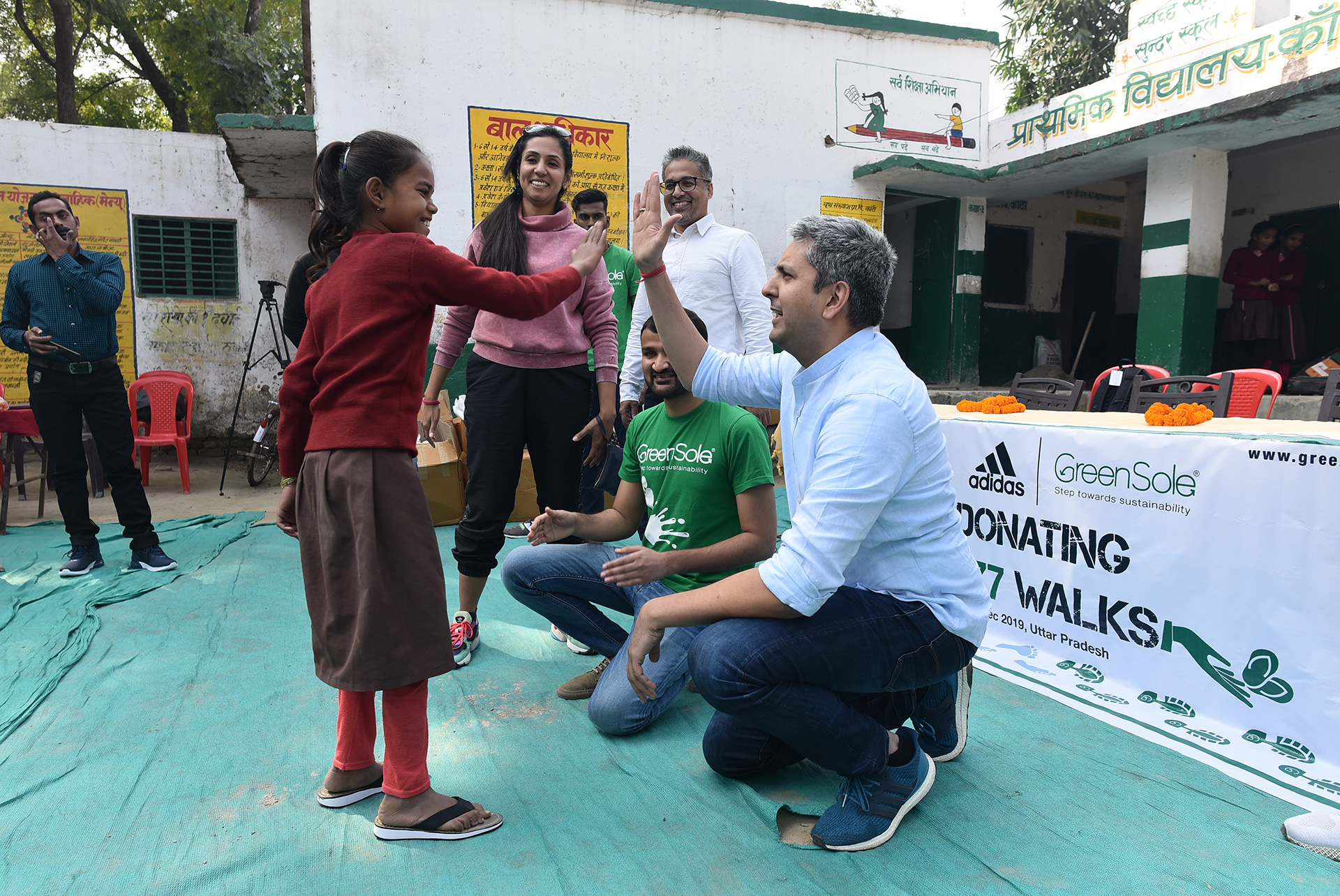 A child being presented with comfortable slippers by Neelandra Singh, Managing Director of Adidas India | Adidas India | Greensole | STIRworld