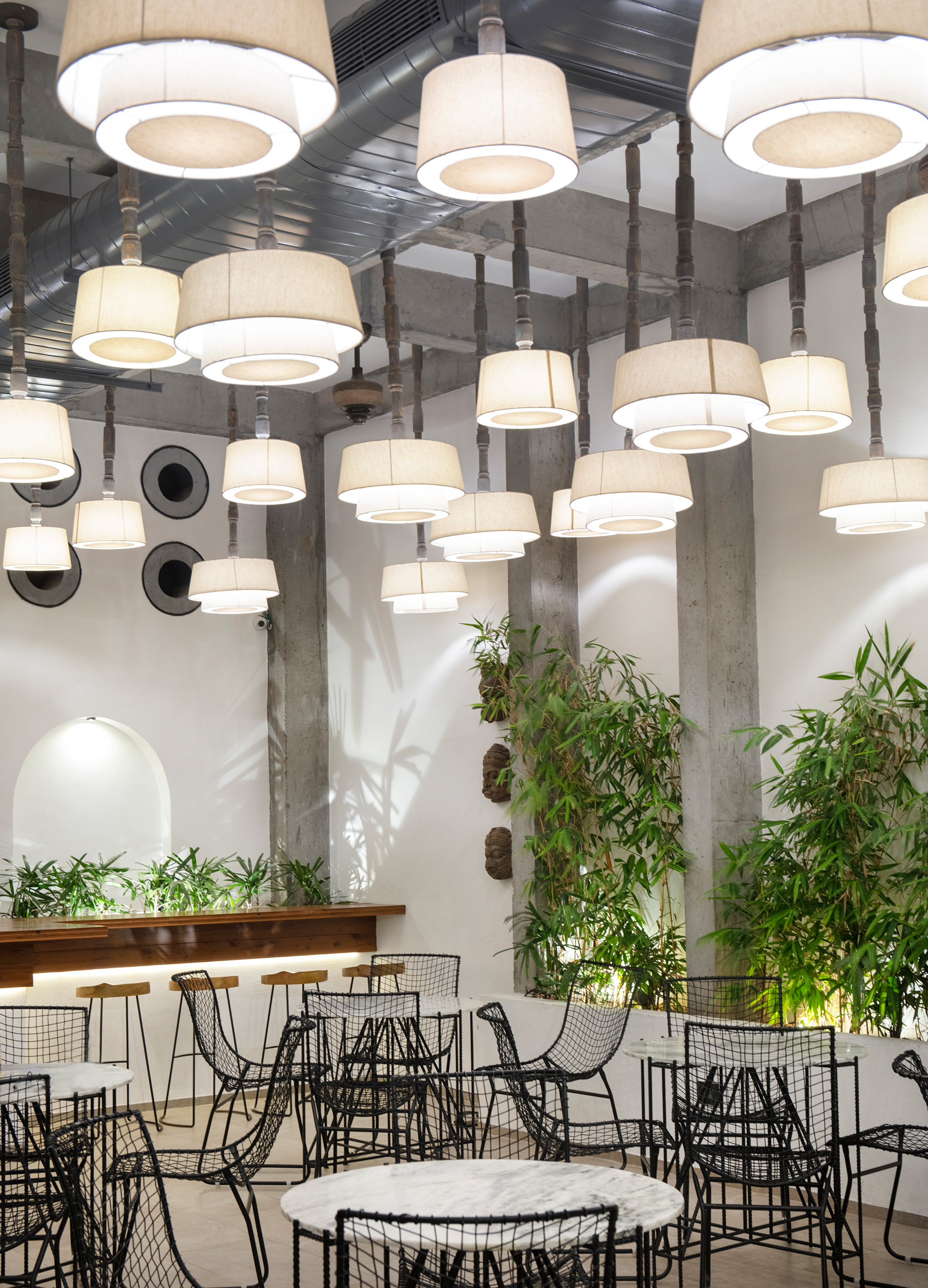 Customised pendant lamps in the interiors render a soft illumination, while light filtered through planters draw abstract silhouettes on walls | The Village Café | Portal 92 | STIRworld