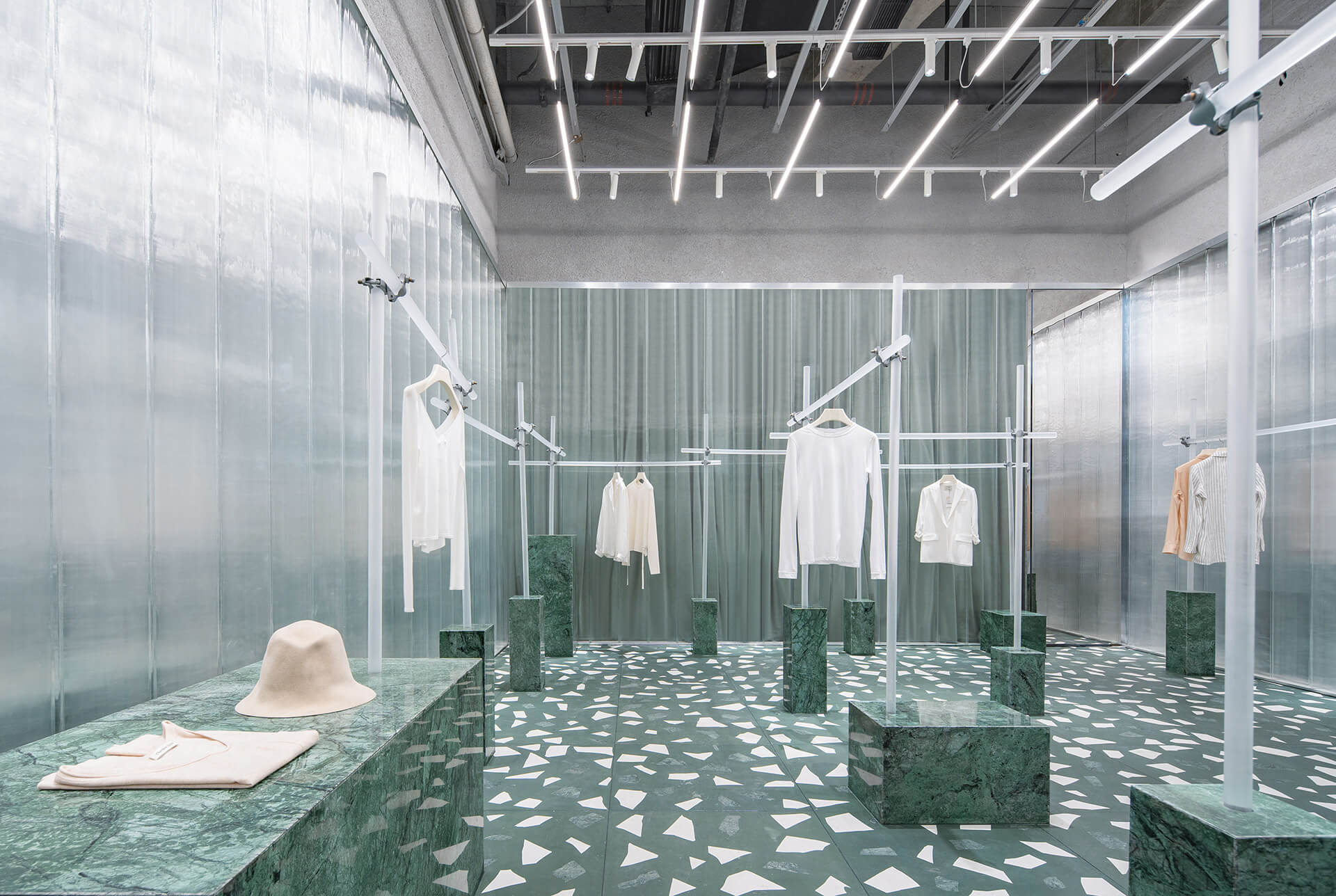 Frosted acrylic rods connected with silver scaffolding metal joints are used to display clothes | Geijoeng Concept Store | Studio 10 | STIRworld