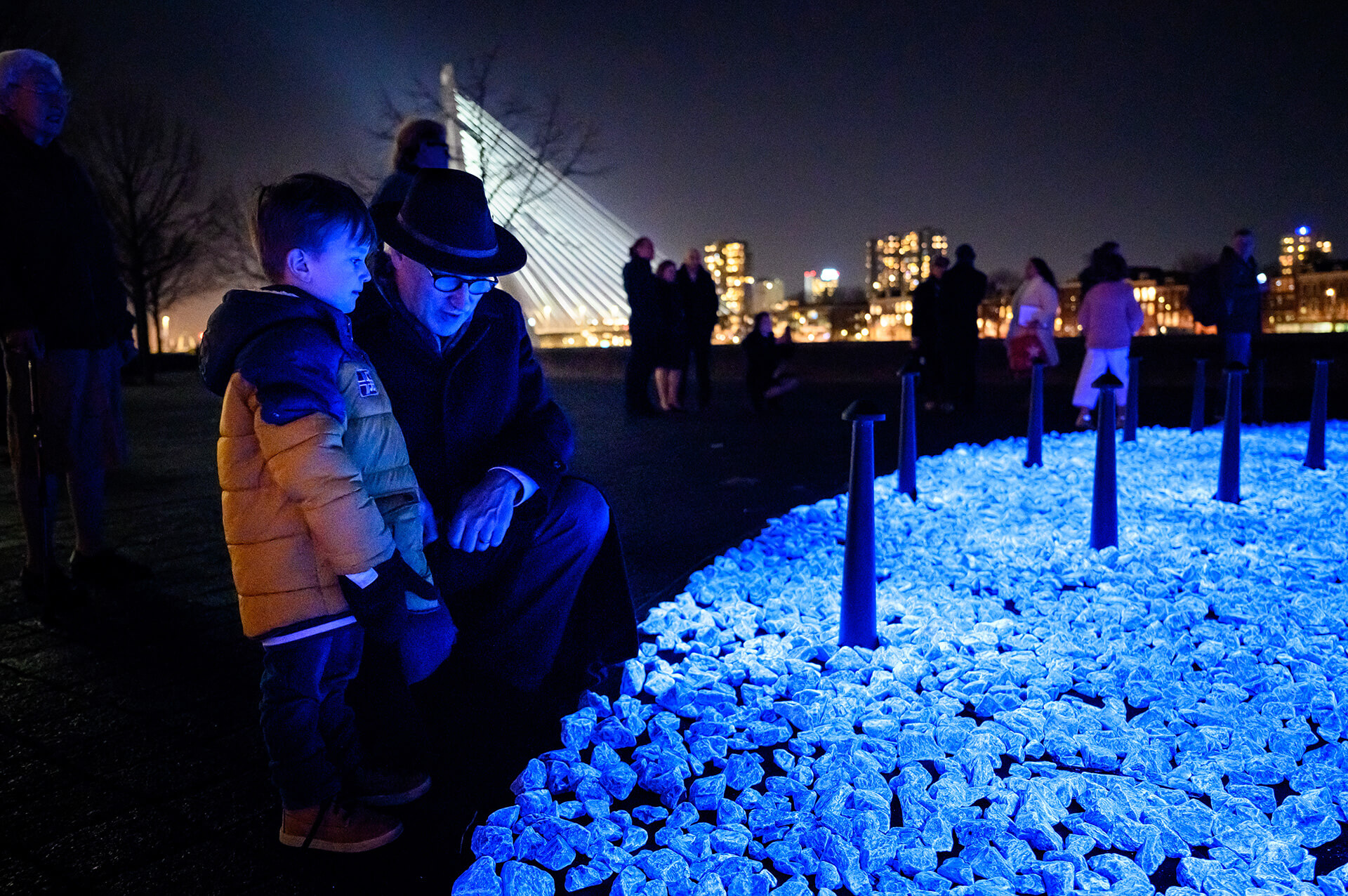 The light-emitting rocks are symbolic of the Jewish custom of placing stones on graves – an elder and child at Levenslicht | Levenslicht | Daan Roosegaarde | Studio Roosegaarde| STIRworld