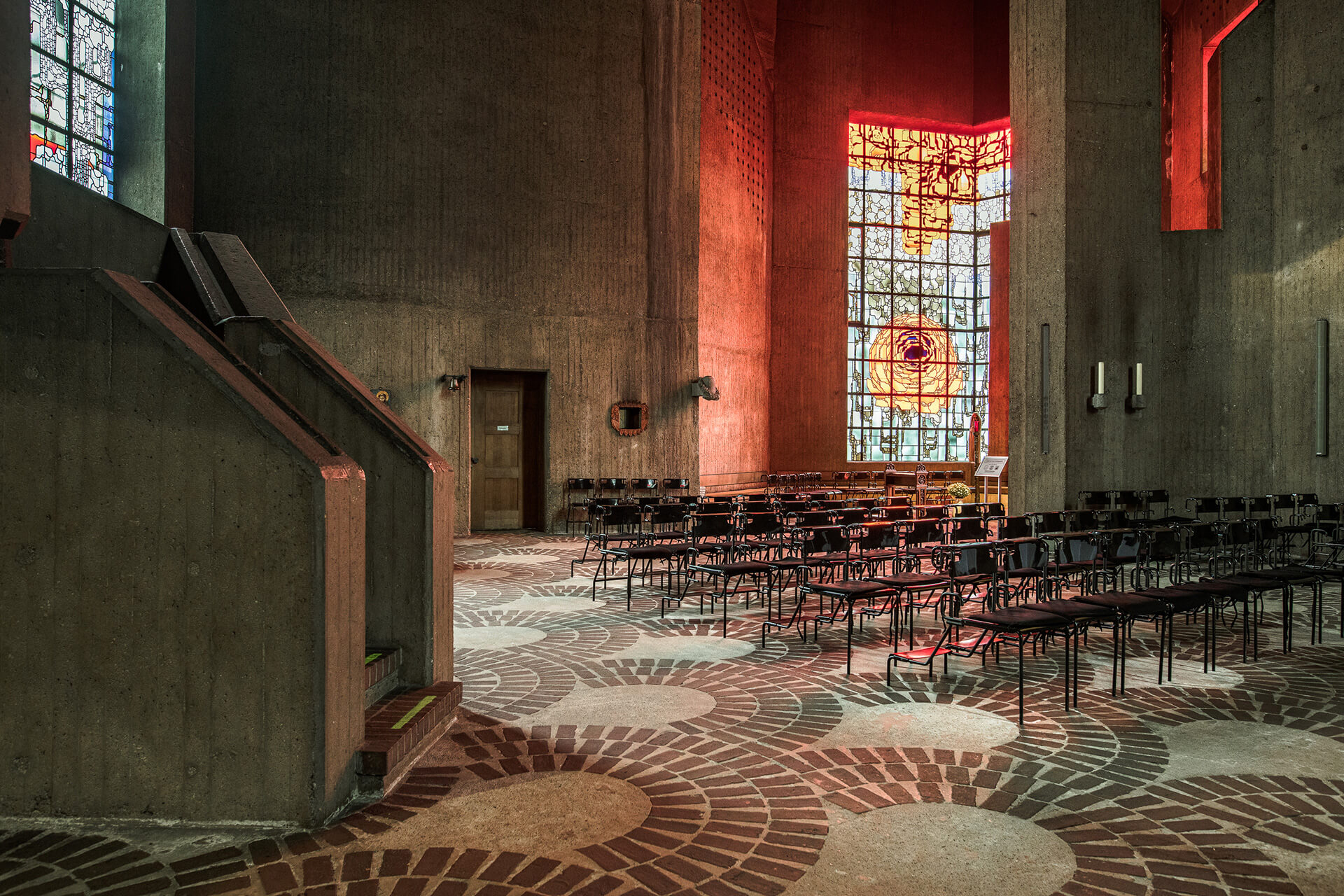 The concrete expanse of the cathedral is punctuated with windows in red stained glass that exude light and warmth | BÖHM100: The Concrete Cathedral of Neviges | Deutsches Architekturmusem (DAM) | STIRworld