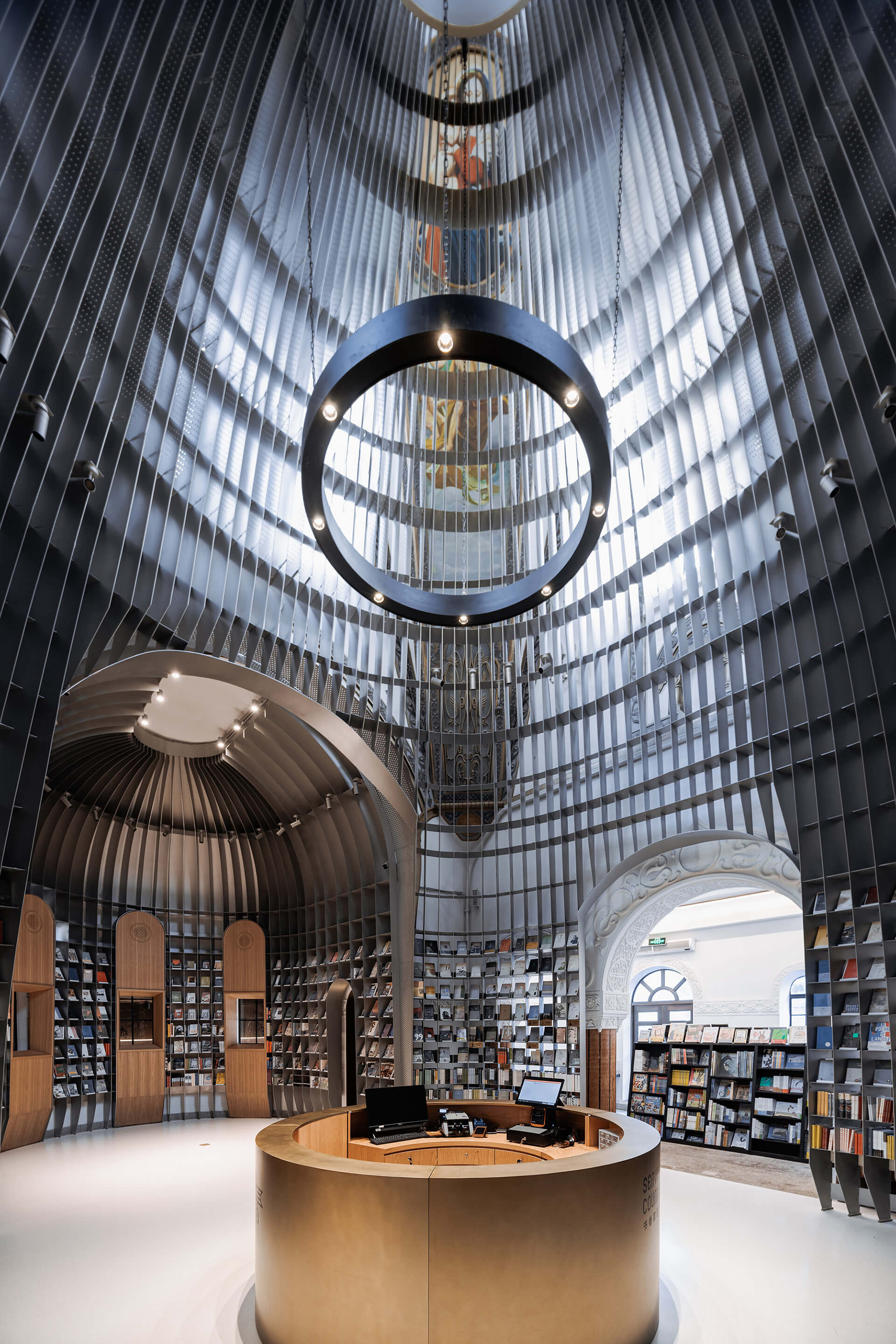 Faint traces of the old frescoes on the wall are revealed through the gridded steel framework | Sinan Books Poetry Store by Wutopia Lab | STIRworld