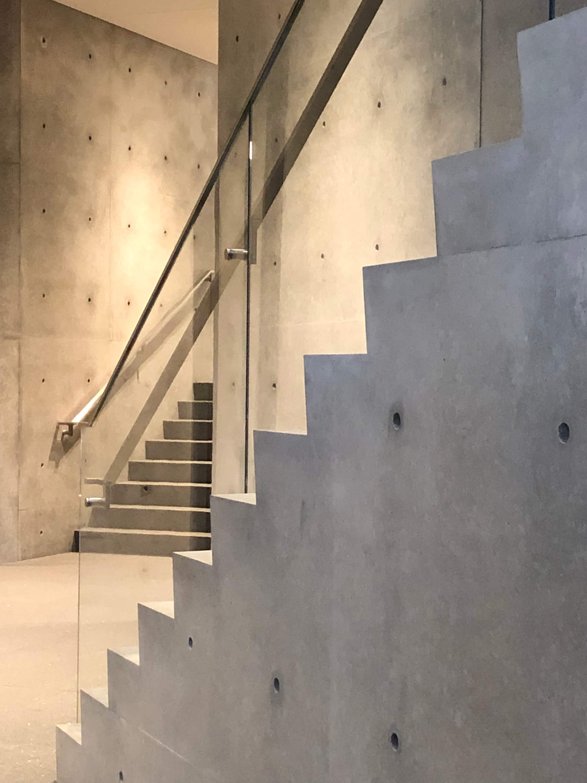 A concrete staircase wraps around a pillar of the same material and provides the primary circulation up the atrium | Wrightwood 659 | Tadao Ando | STIRworld