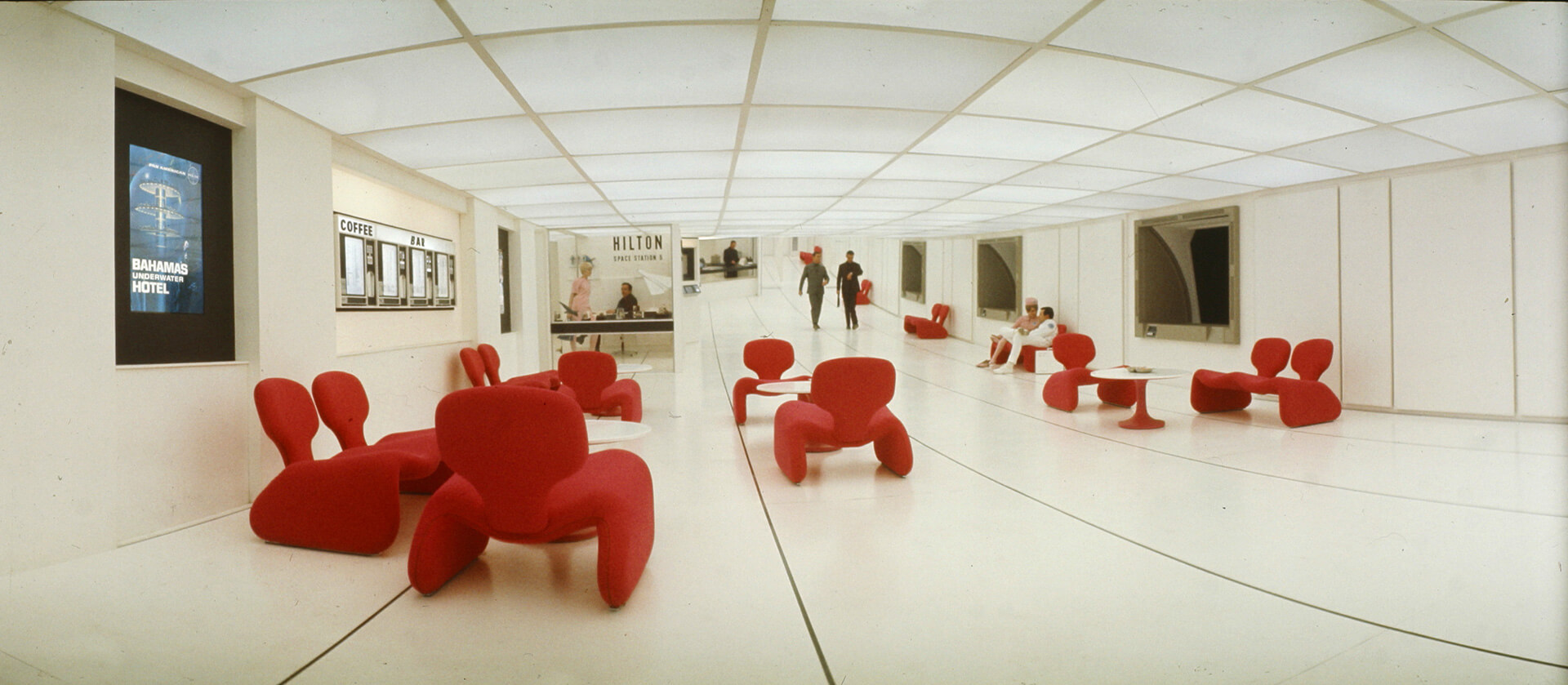 A scene on Space Station V, with red Djinn chairs, in 2001: A Space Odyssey (1968, Dir. Stanley Kubrick) | Space Odyssey exhibition | Stanley Kubrick | STIRworld