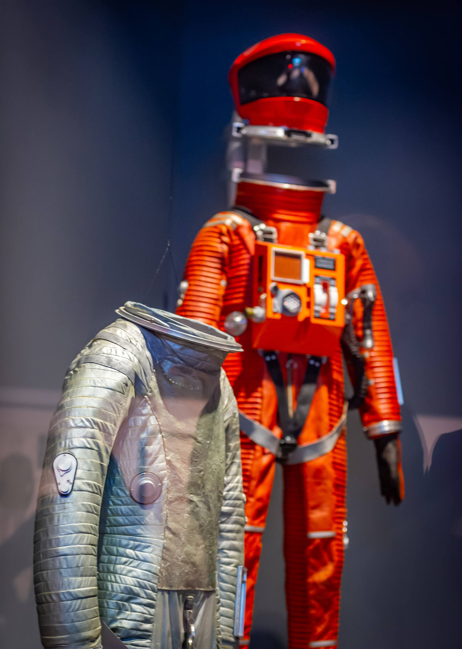 Costumes from 2001: A Space Odyssey: Clavius Moon Base spacesuit (silver) (designed by Harry Lange) and Discovery space suit (red/orange) (designed by Harry Lange) | Space Odyssey exhibition | Stanley Kubrick | STIRworld